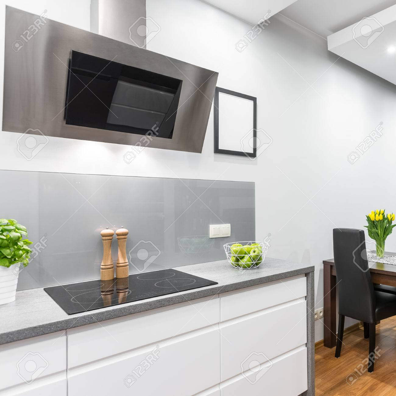 White Kitchen With Induction Hob And Exhaust Hood, Open To A.. Stock ...