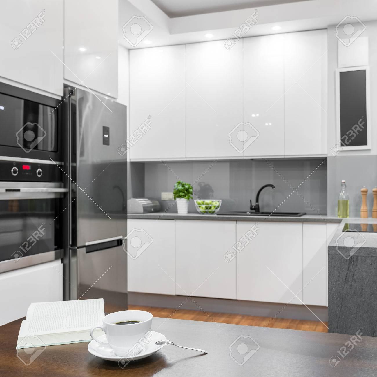 Tazza di caffè sul tavolo da pranzo in legno in piedi in una cucina bianca  lucida