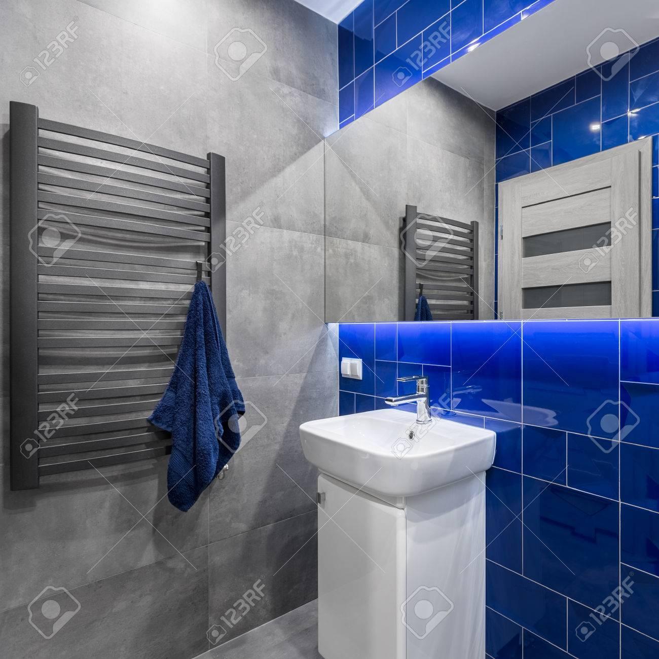 Légante salle de bain avec meuble vasque, miroir, radiateur et carrelage en  gris et bleu