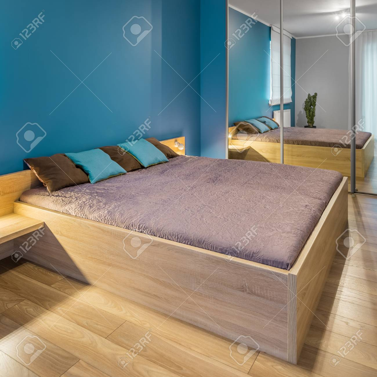 Spacious Blue Bedroom With Big Wooden Bed And Mirrored Wardrobe Stock Photo Picture And Royalty Free Image Image 66148857