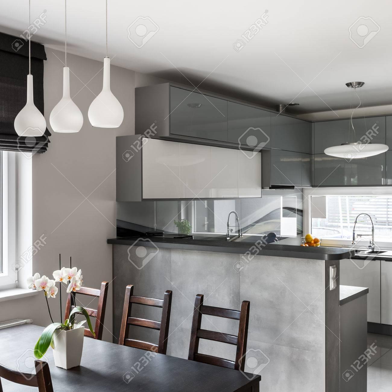 Juego de comedor de madera y lámpara de techo, cocina abierta gris  brillante en el fondo