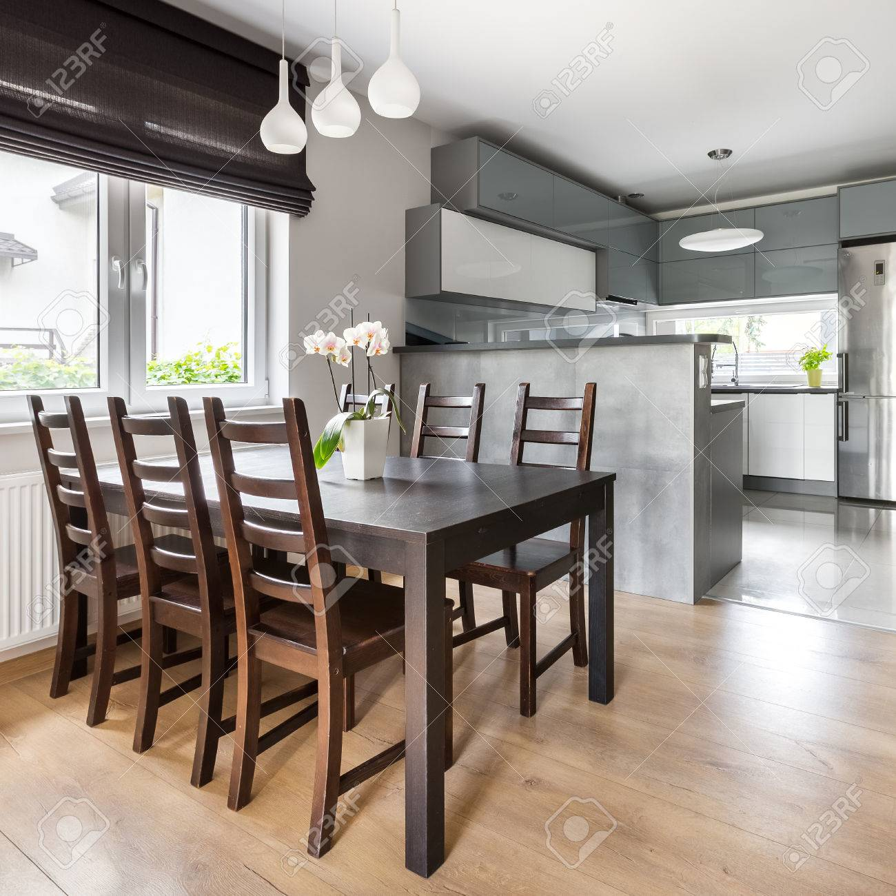 Simple Dining Room With Wooden Table And Light Open Kitchen Stock - Simple-dining-room