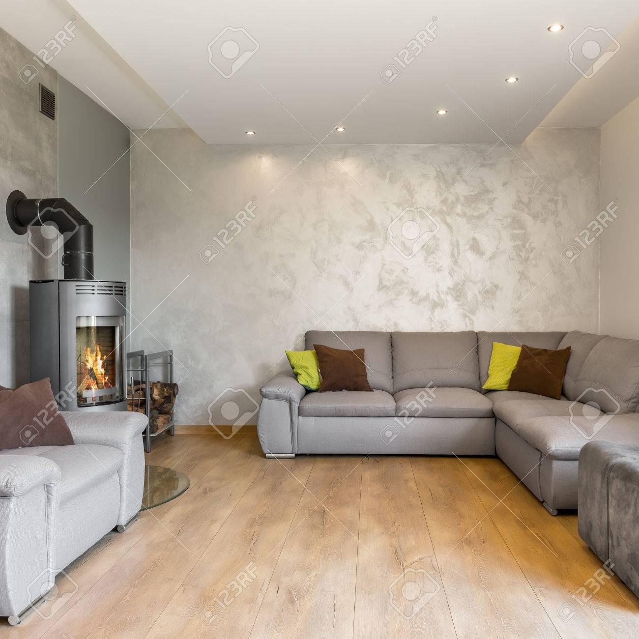 Wohnzimmer In Grau Mit Extra Großem Sofa Und Kamin Im Industriestil ...
