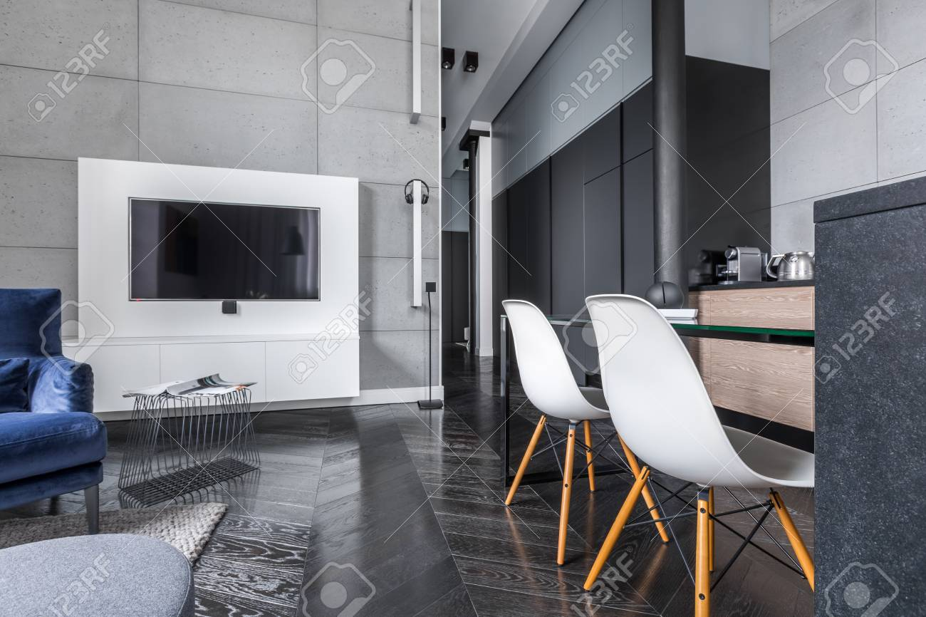 Tv In Modern Living Room With Grey Wall Tiles Open To Kitchen