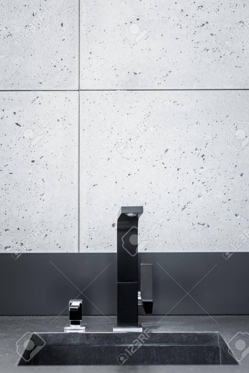 Plan de travail de cuisine noir, évier avec robinet moderne et carreaux de  mur gris
