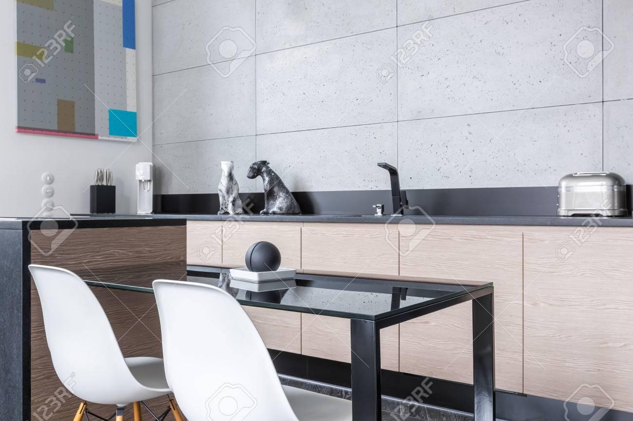 Küche Mit Kochinsel, Einfachen Tisch, Weiße Stühle, Lange Arbeitsplatte Und  Grauen Fliesen Standard