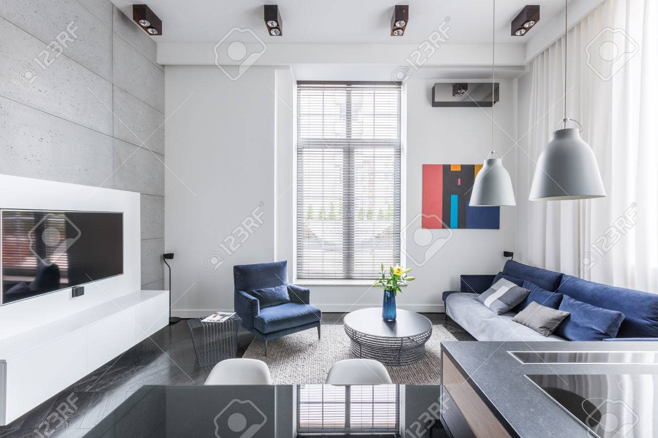 Bianco tv soggiorno con divano e poltrone blu foto royalty free