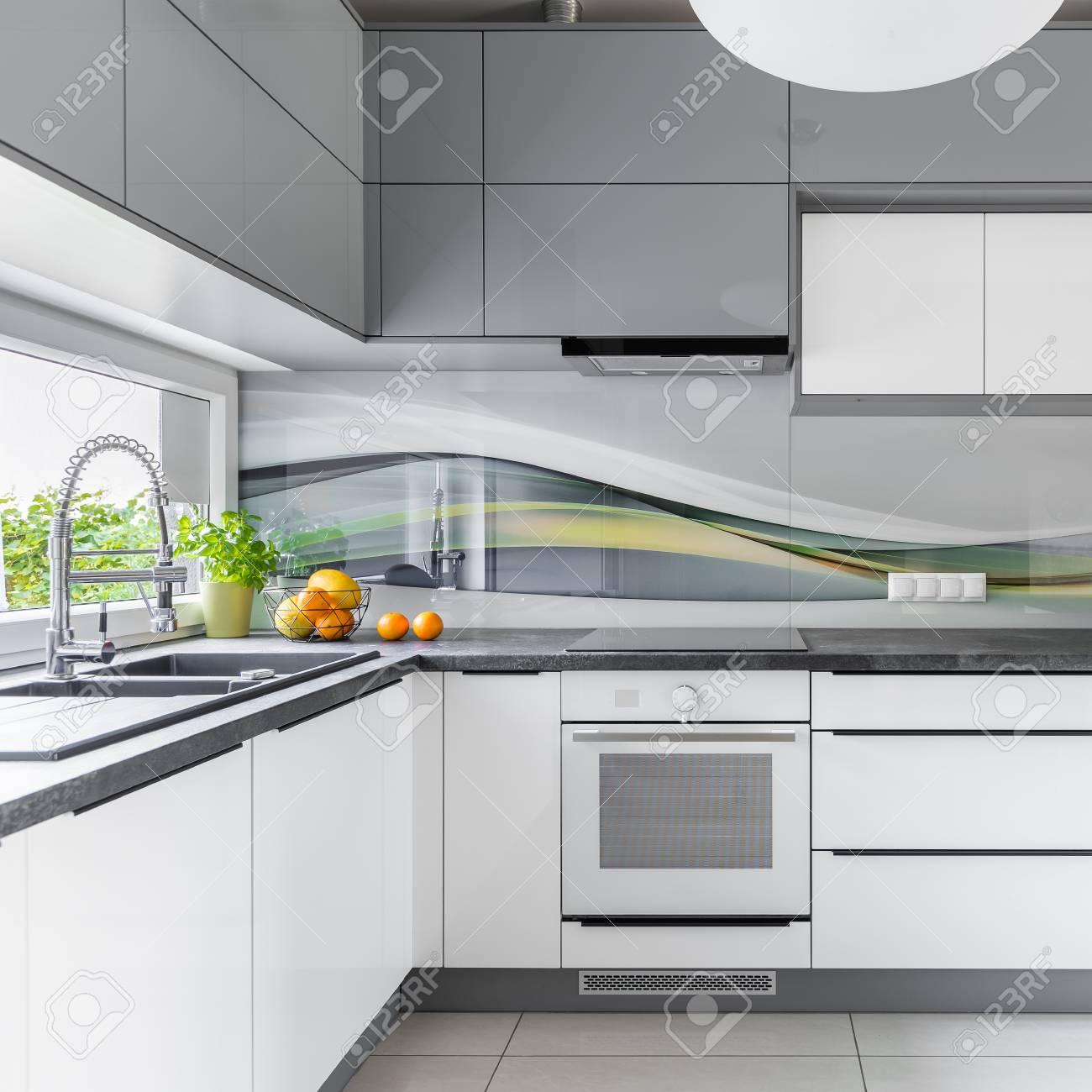 Funktionelle Und Geräumige Küche Mit Fenster, Möbel In Weiß Und Grau  Standard Bild