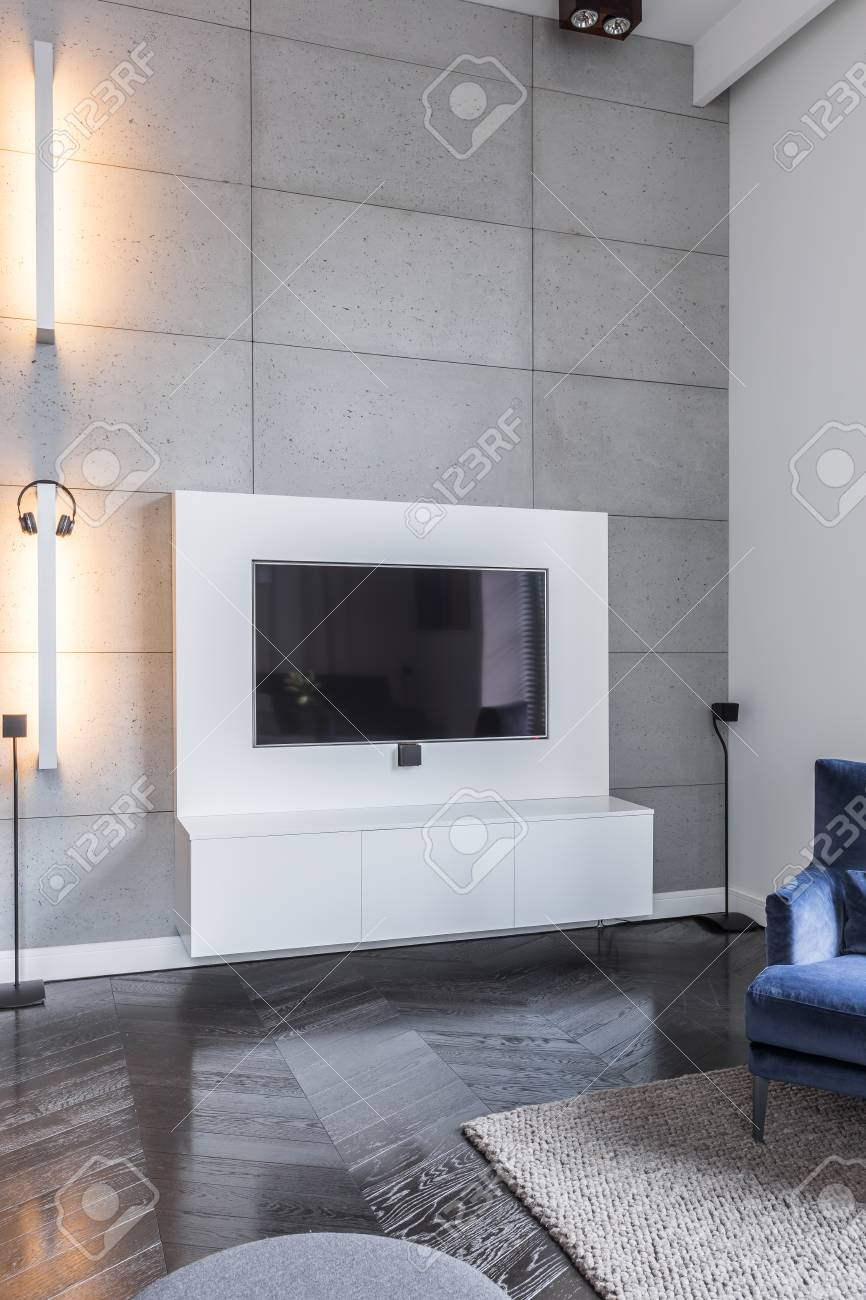 Television in grey living room with wooden floor panels