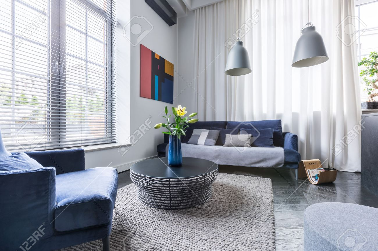 Living room with blue upholstered furniture, window blinds and white net curtain - 69585627