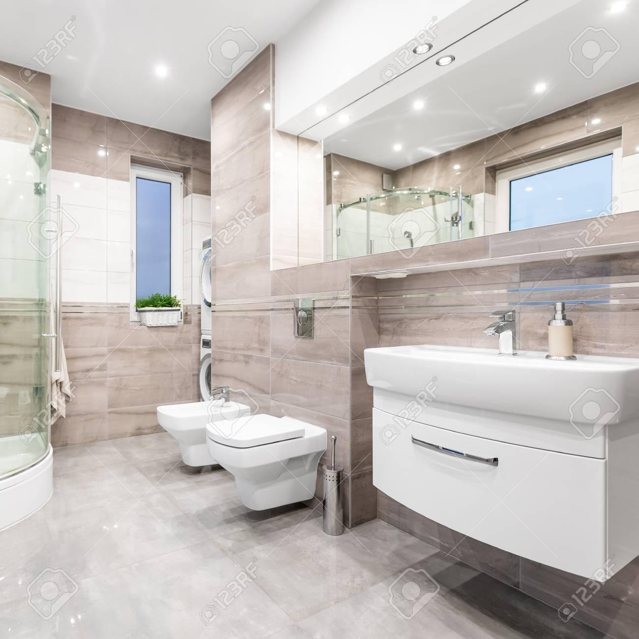 Salle de bain beige fonctionnelle avec fenêtre, douche, toilette, bidet,  lavabo et miroir