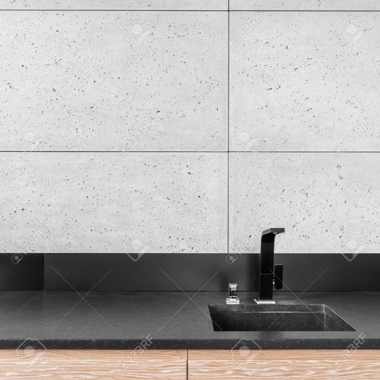 Cuisine moderne avec carrelage mural gris, plan de travail noir, évier et  robinet