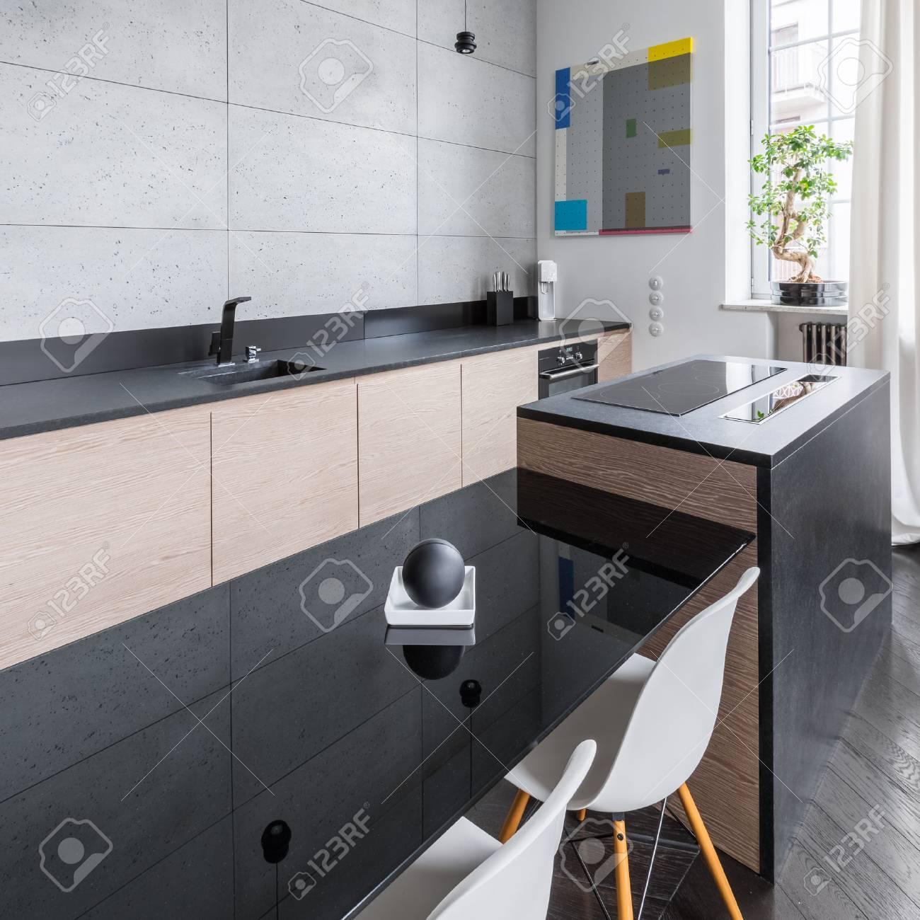 Cuisine moderne et élégante avec comptoir noir et table et chaises blanches