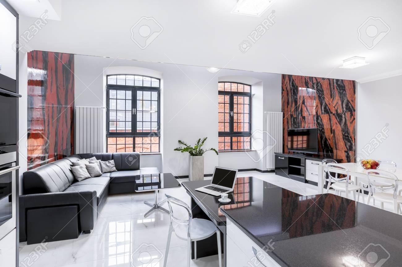 Salon et salle à manger au design moderne avec carrelage mural noir et rouge