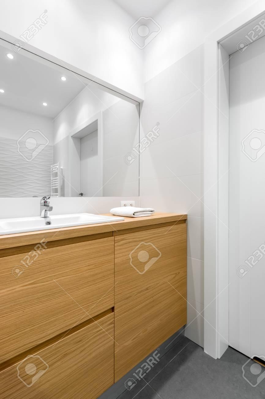 Breiter Spiegel über Holzschränken Im Sauberen, Weißen Badezimmer ...