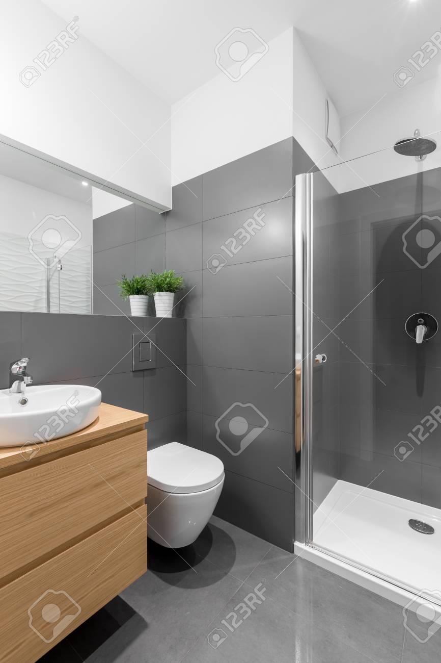 Légante salle de bain grise avec grande douche et meubles en bois