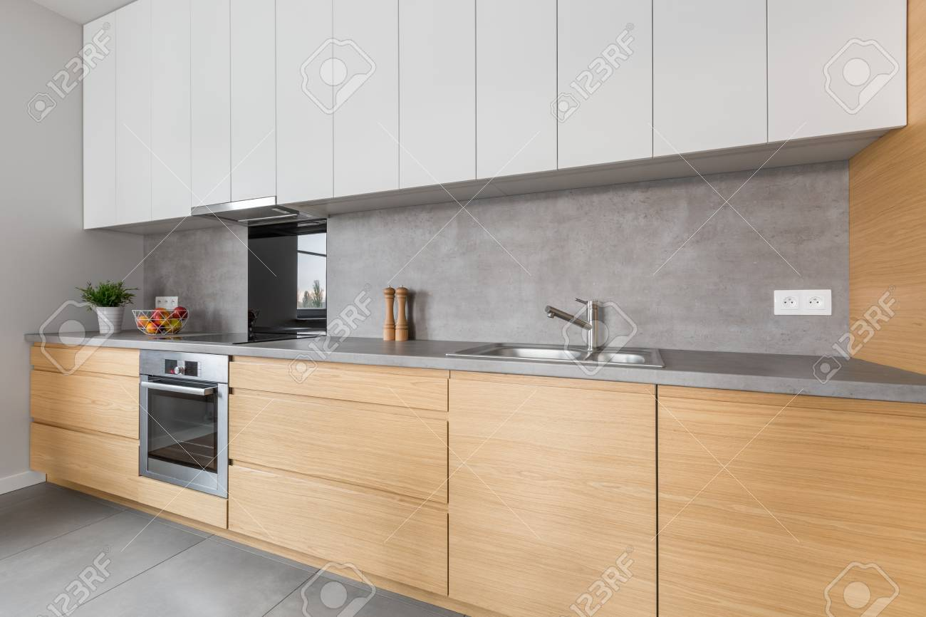 Dos muebles de cocina de color con encimera de hormigón y electrodomésticos  de acero