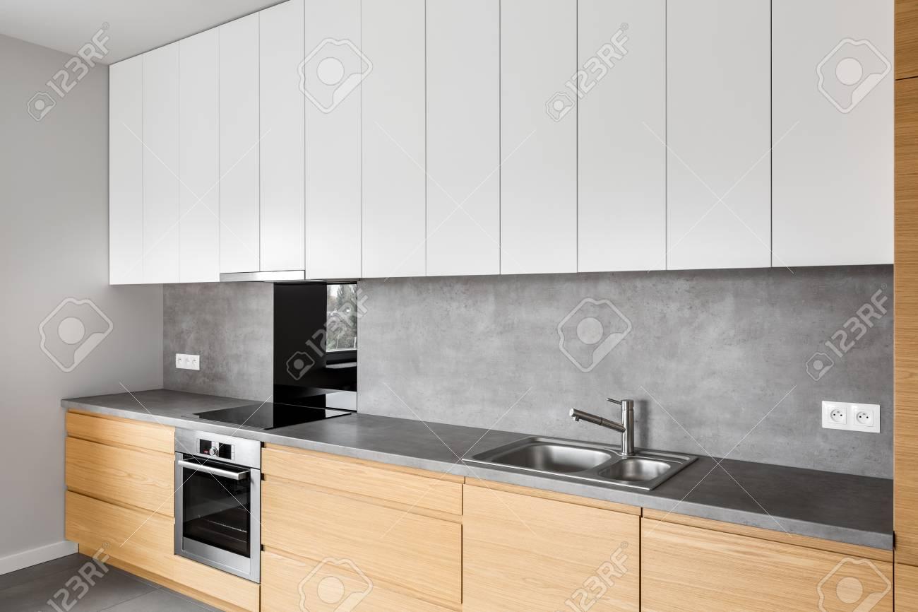Muebles de cocina modernos con utensilios de cocina contemporáneos como  campana, inducción y horno