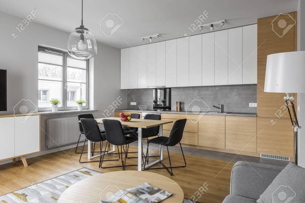 Cocina contemporánea con muebles modernos y mesa grande con sillas negras