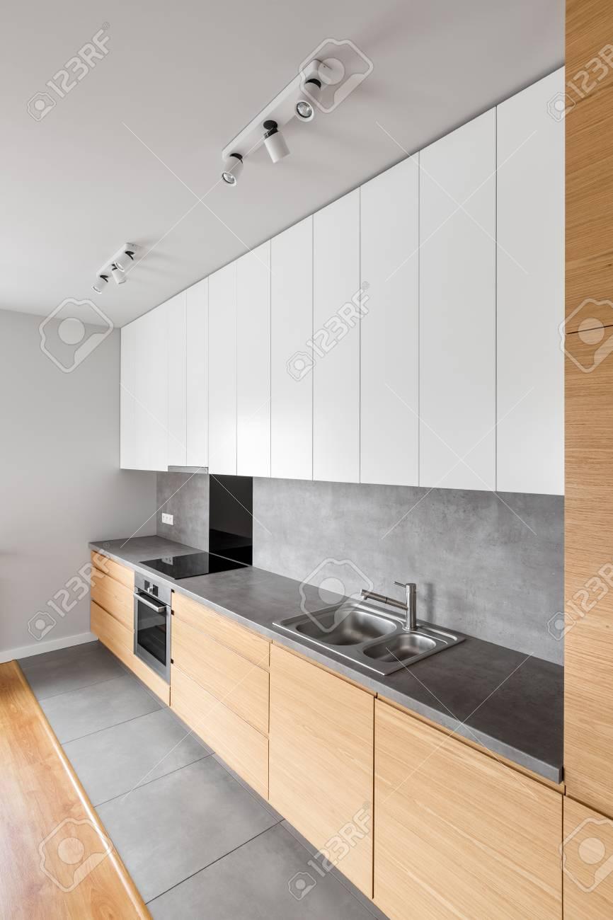 Muebles de cocina contemporáneos con encimera larga y gris y utensilios de  cocina modernos