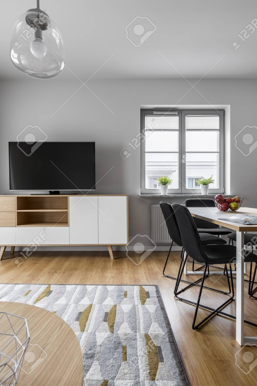 Grey living room with modern lamp, tv, table and carpet
