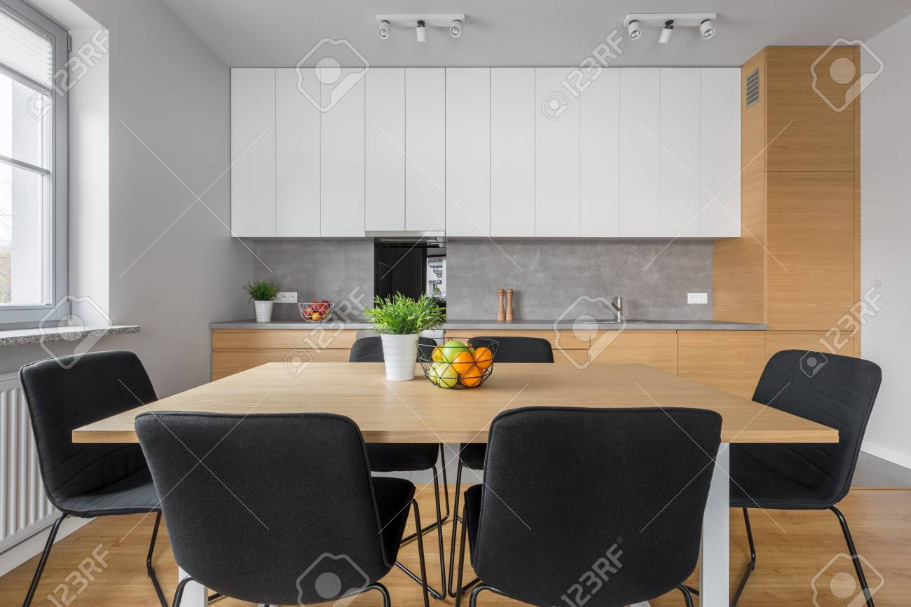 Cocina de diseño moderno y comedor con mesa de madera, sillas negras y luz  de techo