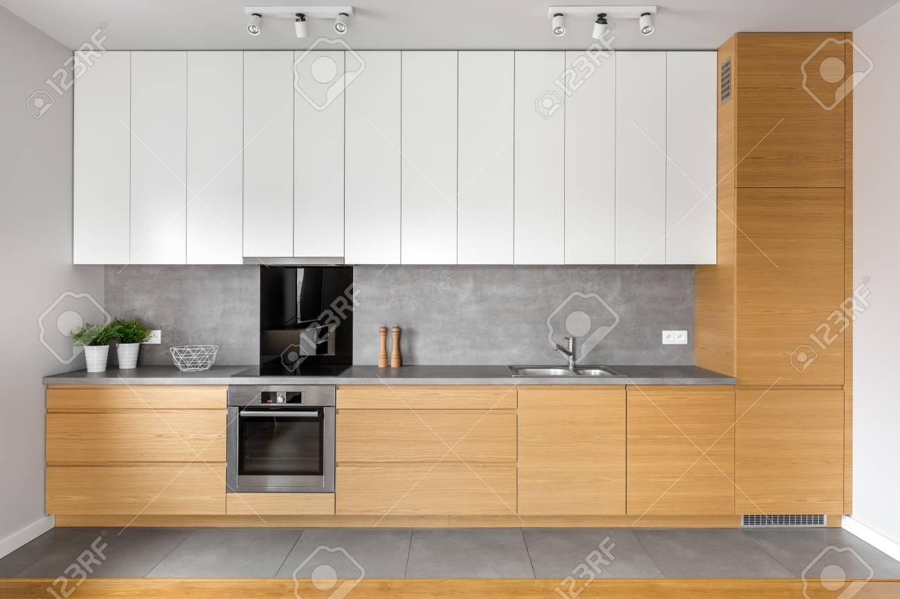 Moderne Küche Mit Grauen Fliesen, Braunen Und Weißen Schränken,  Arbeitsplatte Aus Granit Standard