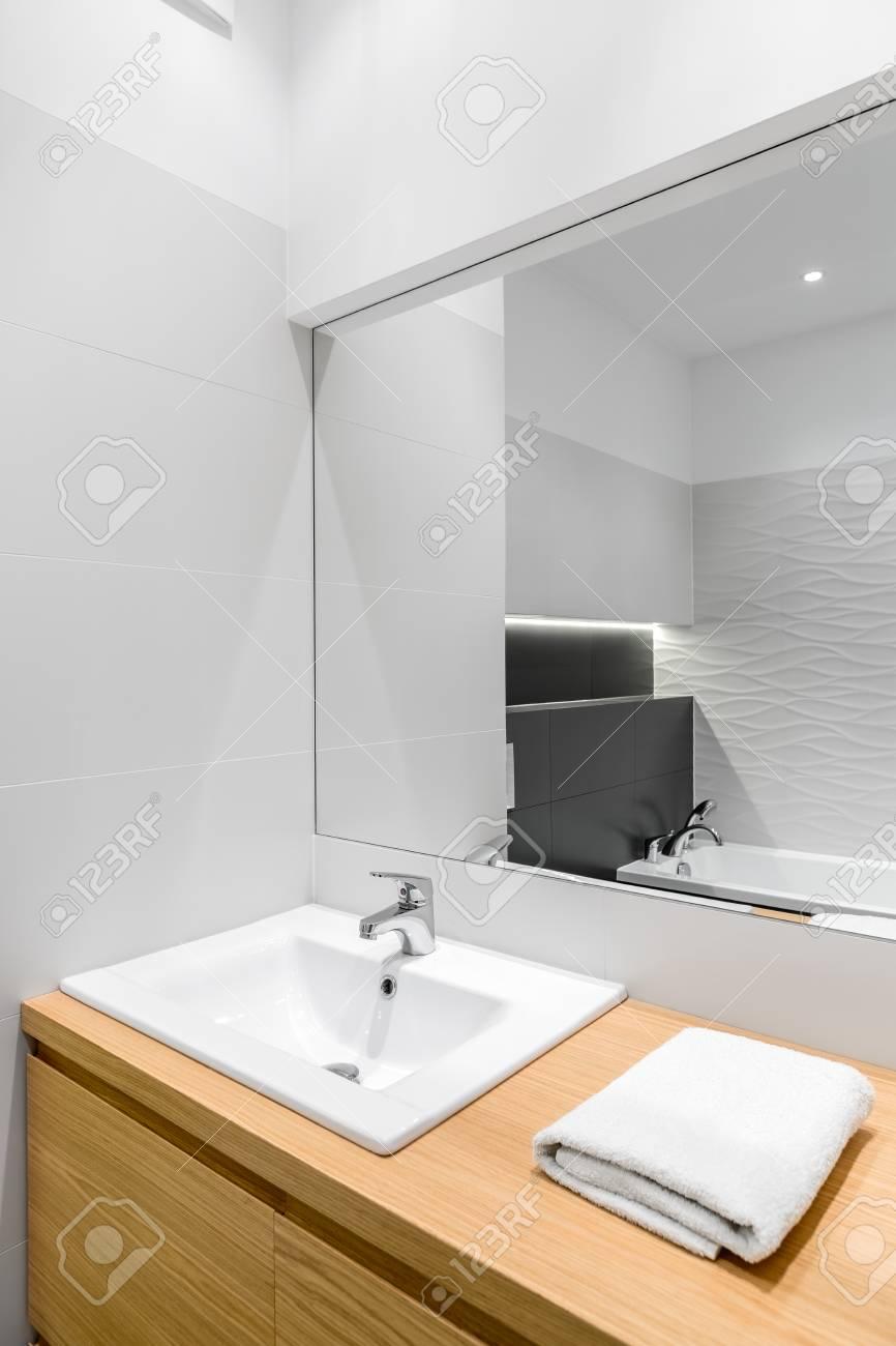 Nouvelle salle de bain blanche avec meuble en bois, bassin élégant et grand  miroir