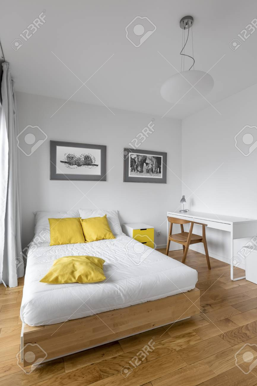 Modern White Bedroom With Big Wooden Bed Desk And Yellow Decorations Stock Photo Picture And Royalty Free Image Image 77776543
