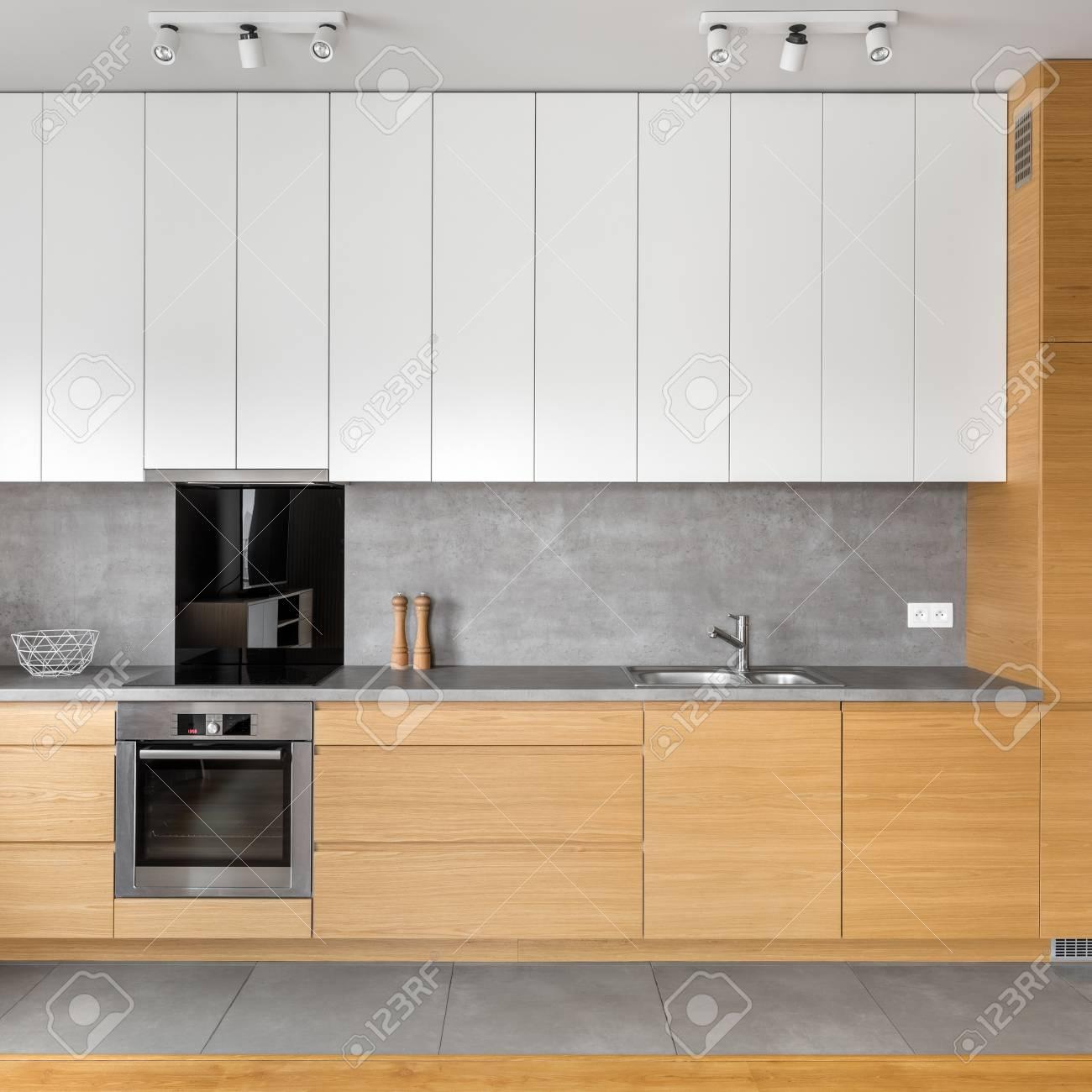 Moderne Küche Mit Grauen Fliesen, Holz- Und Weißen Schränken ...