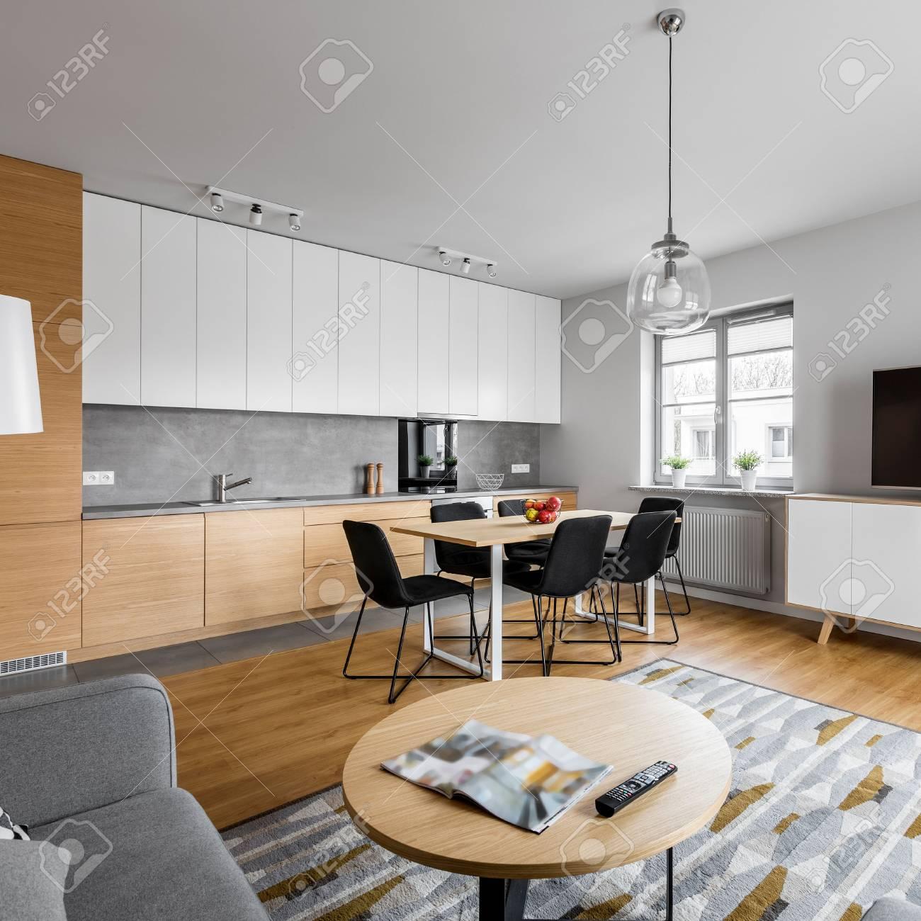 Cocina moderna de espacio abierto con salón y mesa redonda.