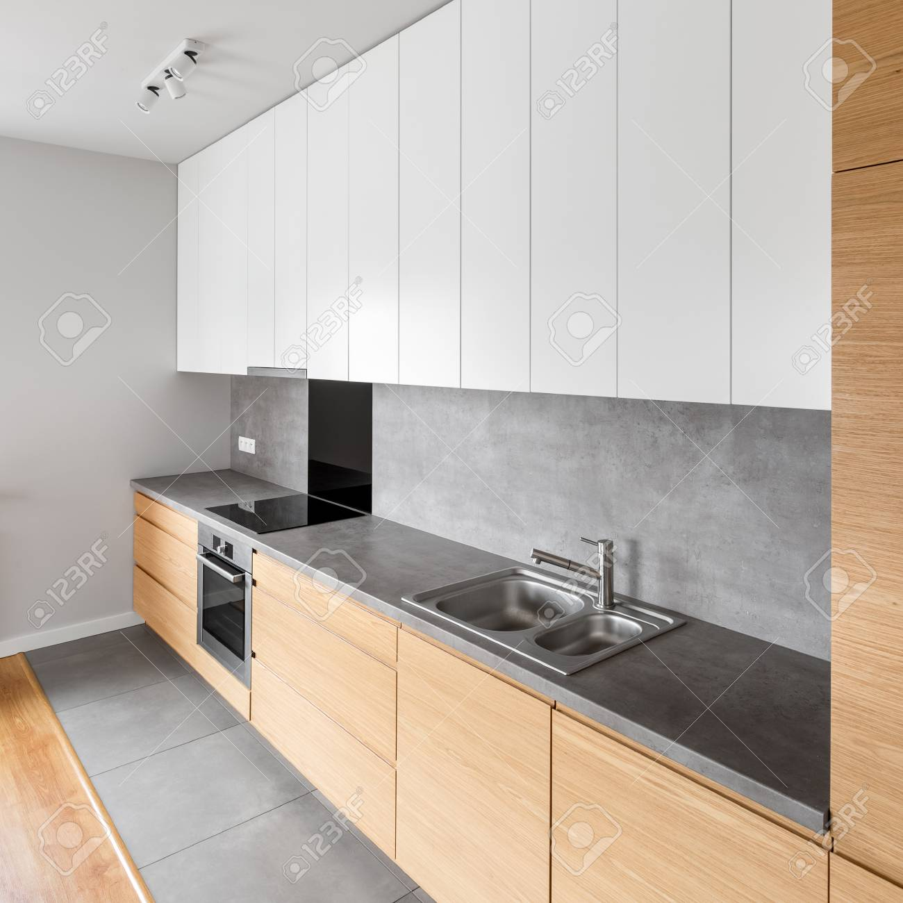 Contemporary Kitchen With Long Grey Countertop And Modern Cupboard