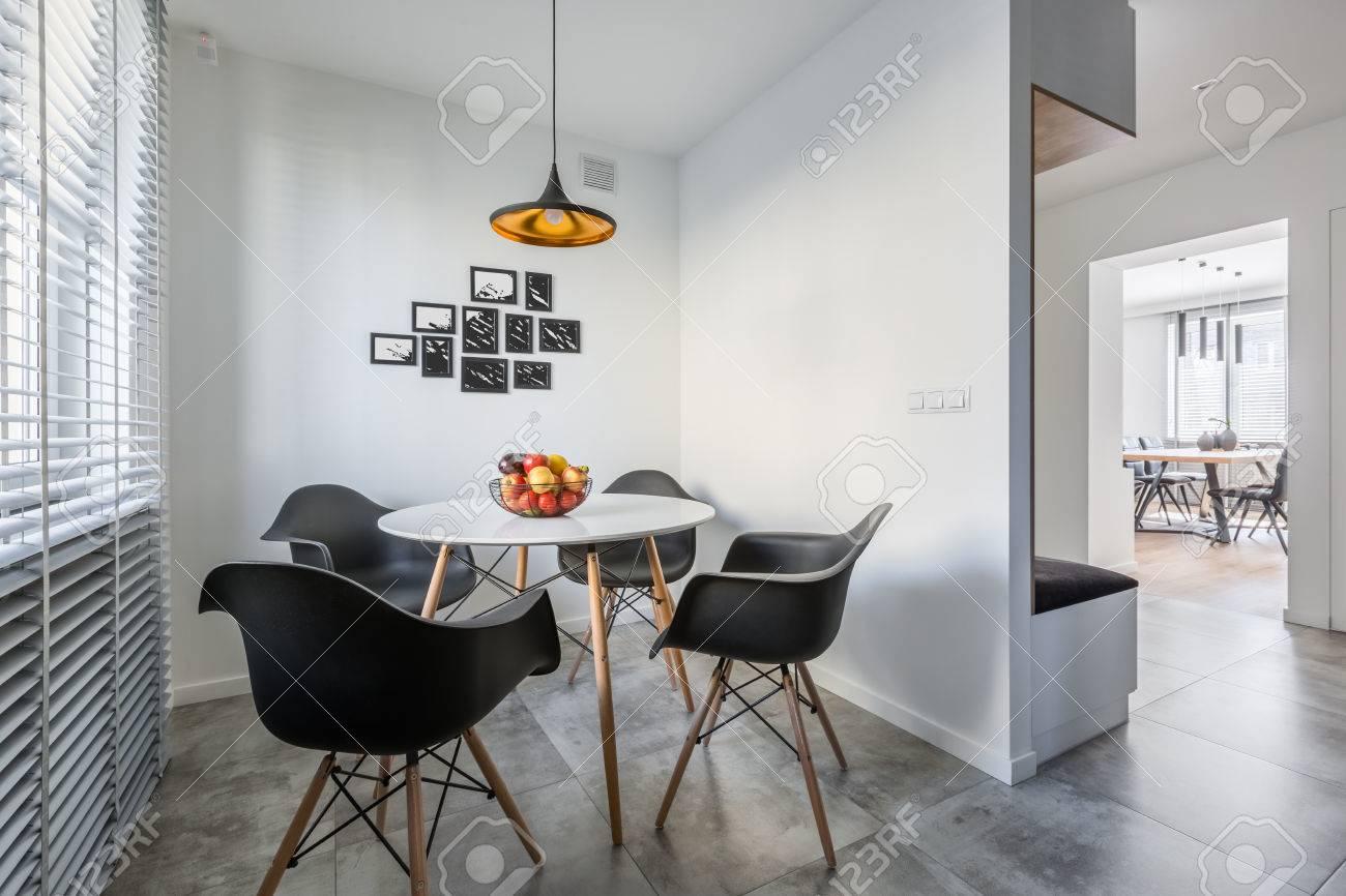 Interno bianco della casa con lampada, tavolo rotondo moderno e sedie nere