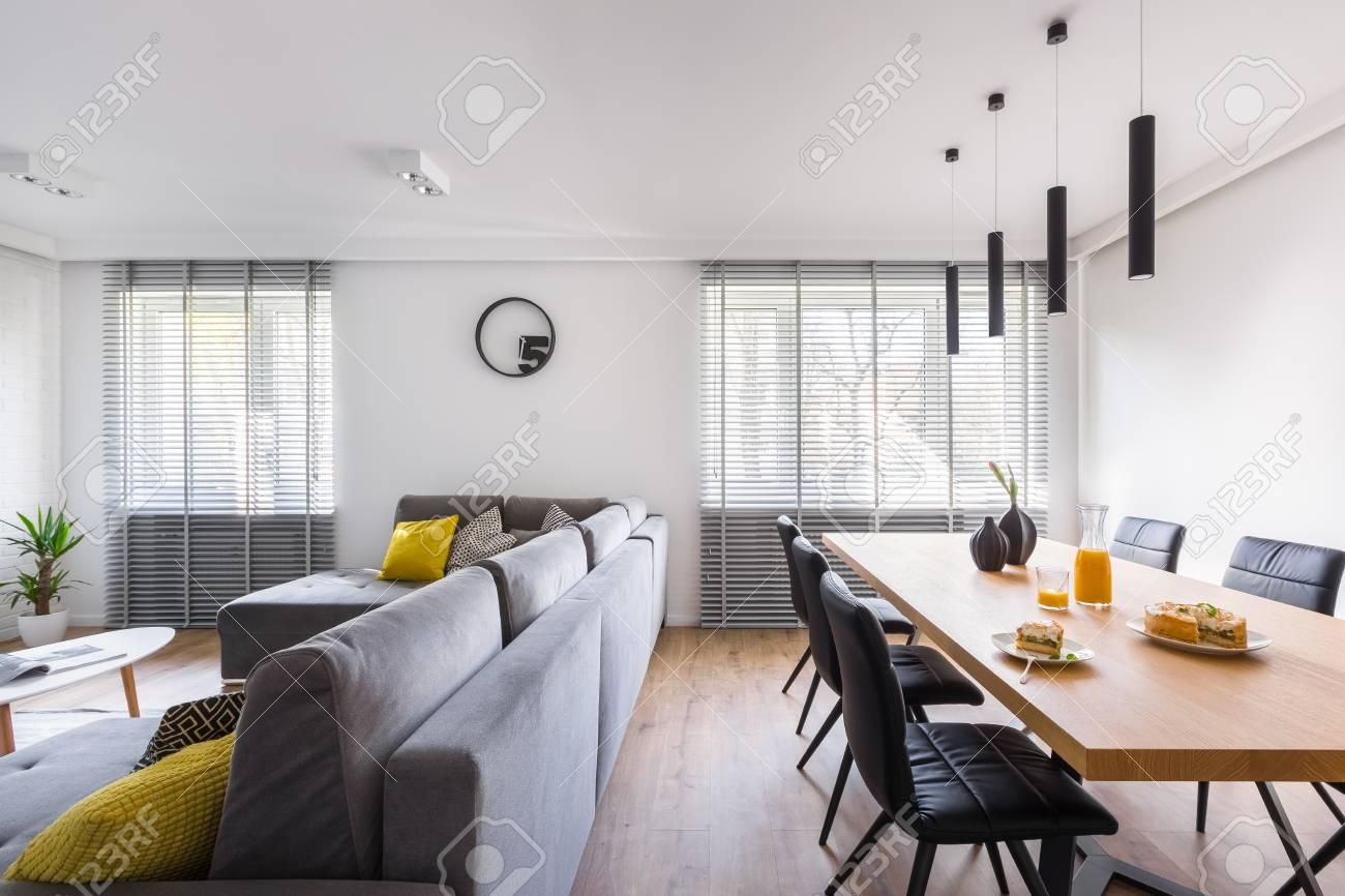 Intérieur de maison moderne avec table commune, chaises noires et canapé  extra large gris