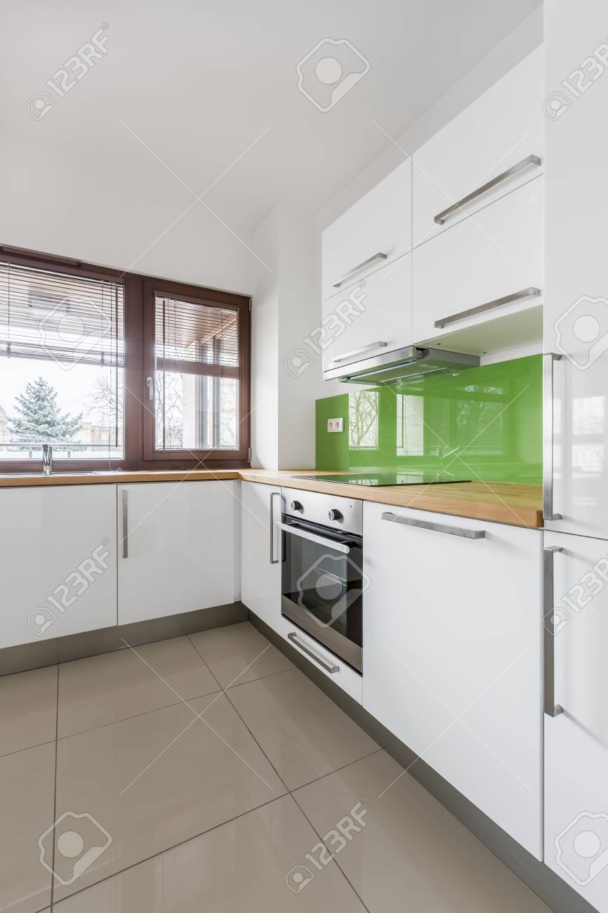 White Kitchen With Modern Cupboards Beige Floor Tiles And Big