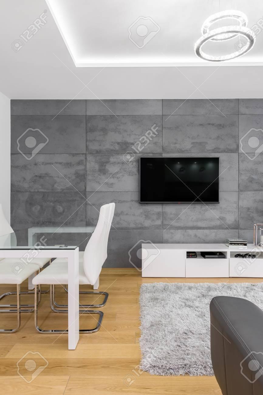 Salon gris et blanc avec table, télévision et chaise