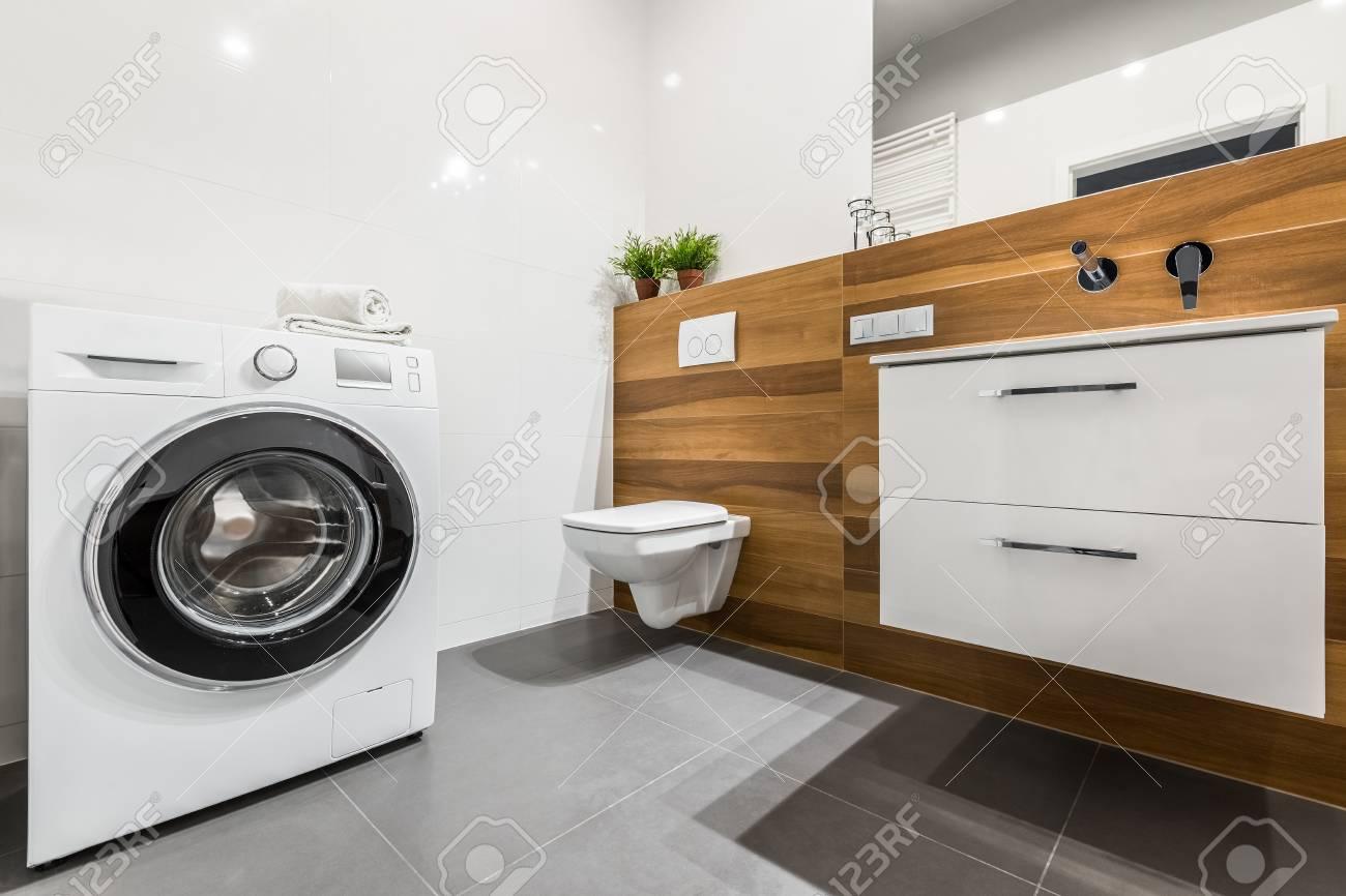 Holzbadezimmer mit weißer fliesen waschmaschine schrank und wc