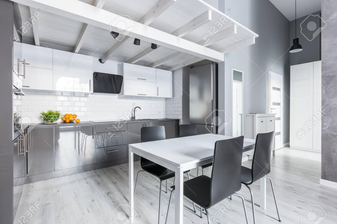 Cuisine grise avec table à manger blanche et chaises noires