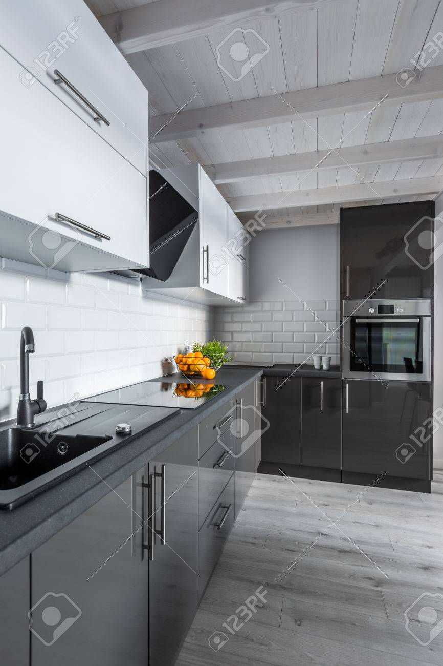Modern Black And White Kitchen With Wooden Ceiling Stock Photo