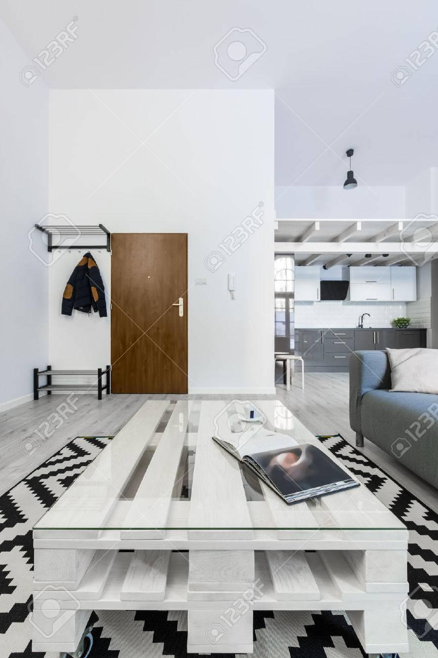 weißes wohnzimmer mit diy palettentisch und musterteppich