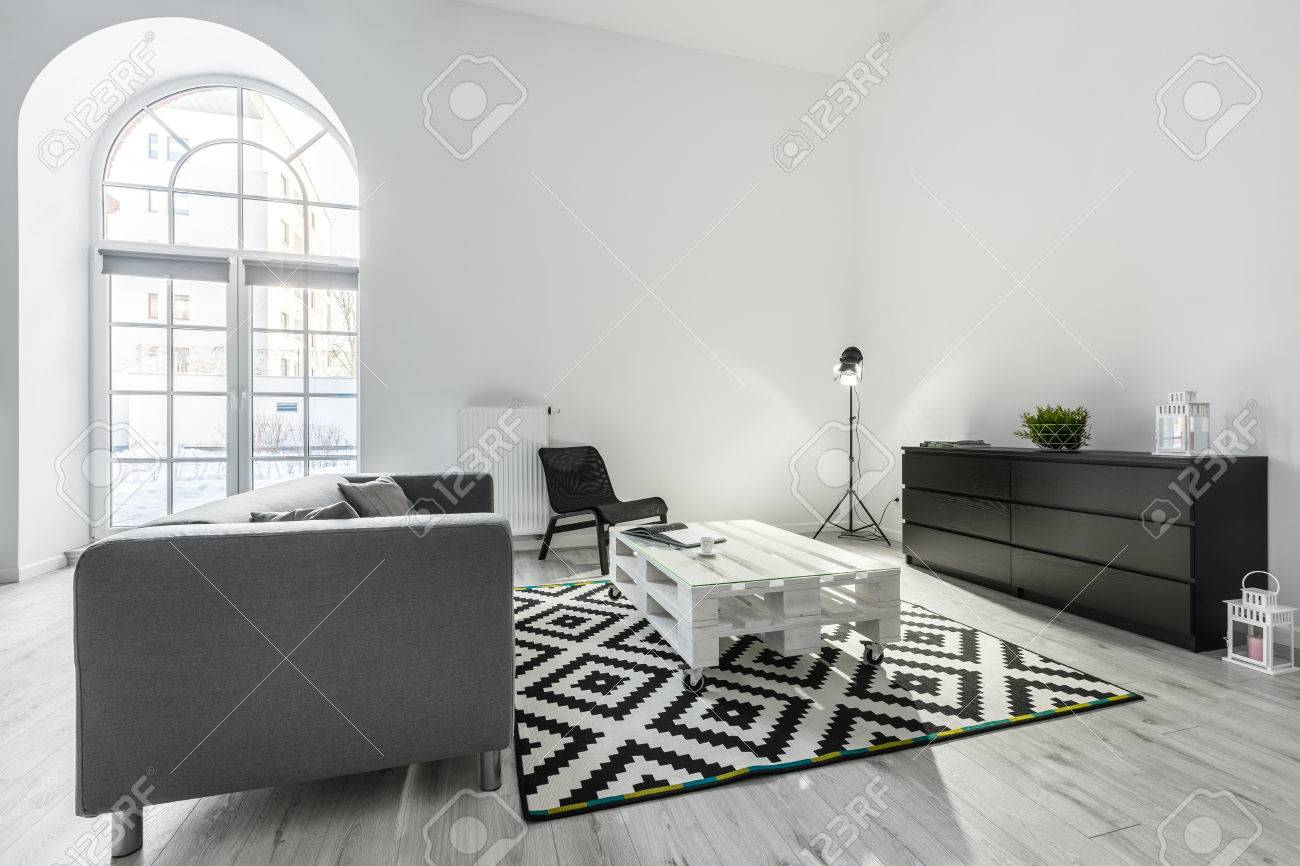 White living room with gray sofa, pallet table and black cabinet
