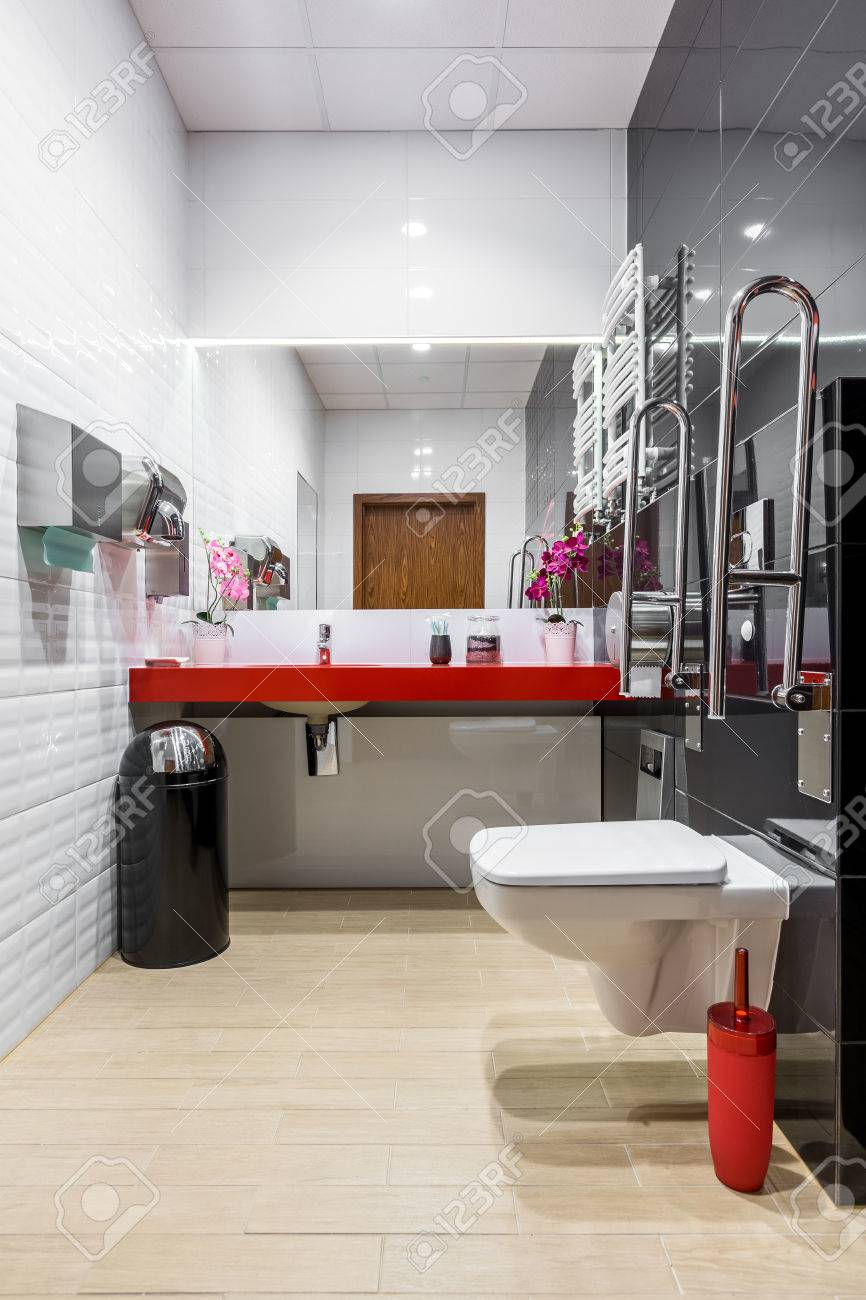 Black And White Modern Bathroom With Toilet, Red Countertop And Safety Grab  Bars Stock Photo