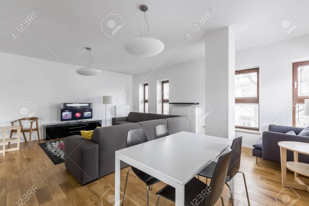 Salle à manger ouverte avec table moderne et blanche et chaises noires