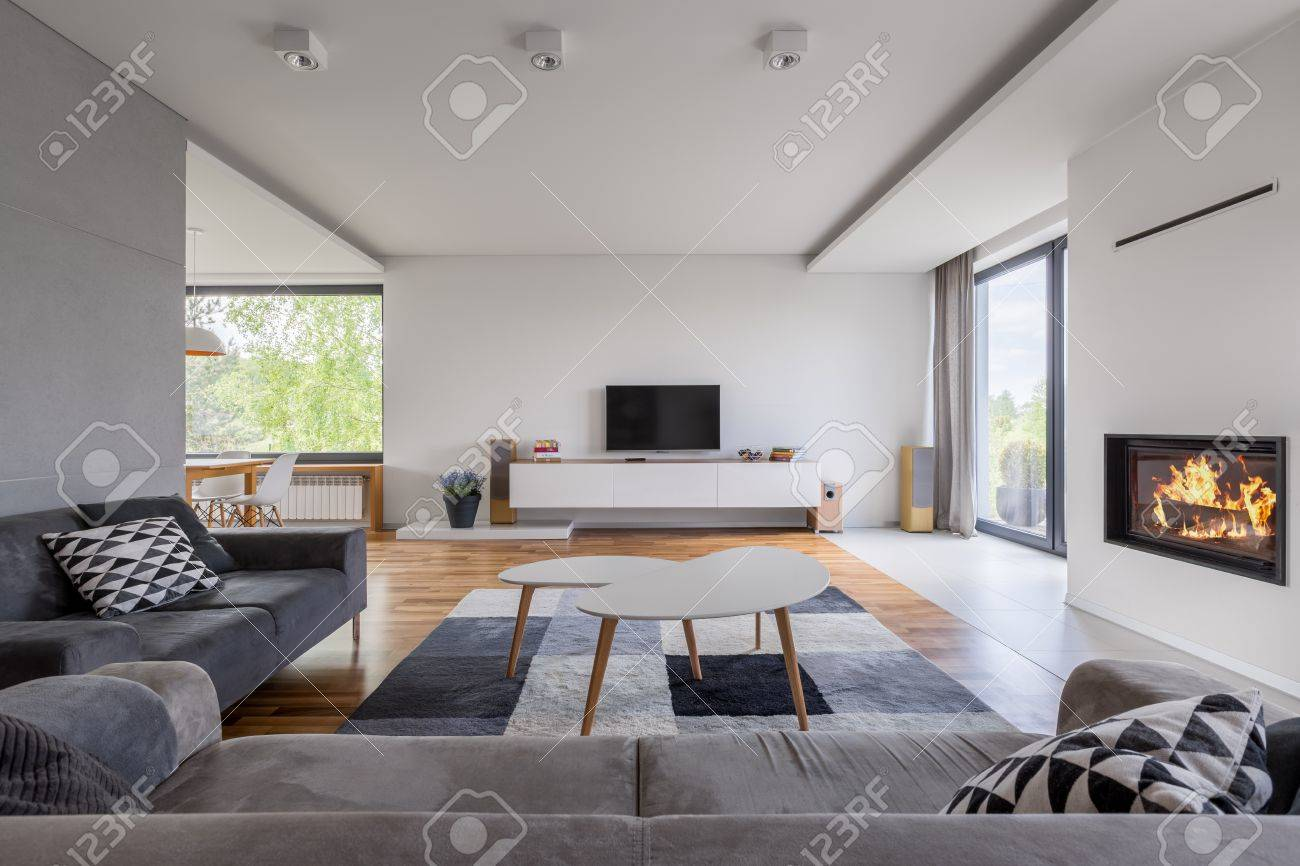 Grau Und Weiß, Familien Wohnzimmer Mit Kamin, TV Und Sofa Standard Bild