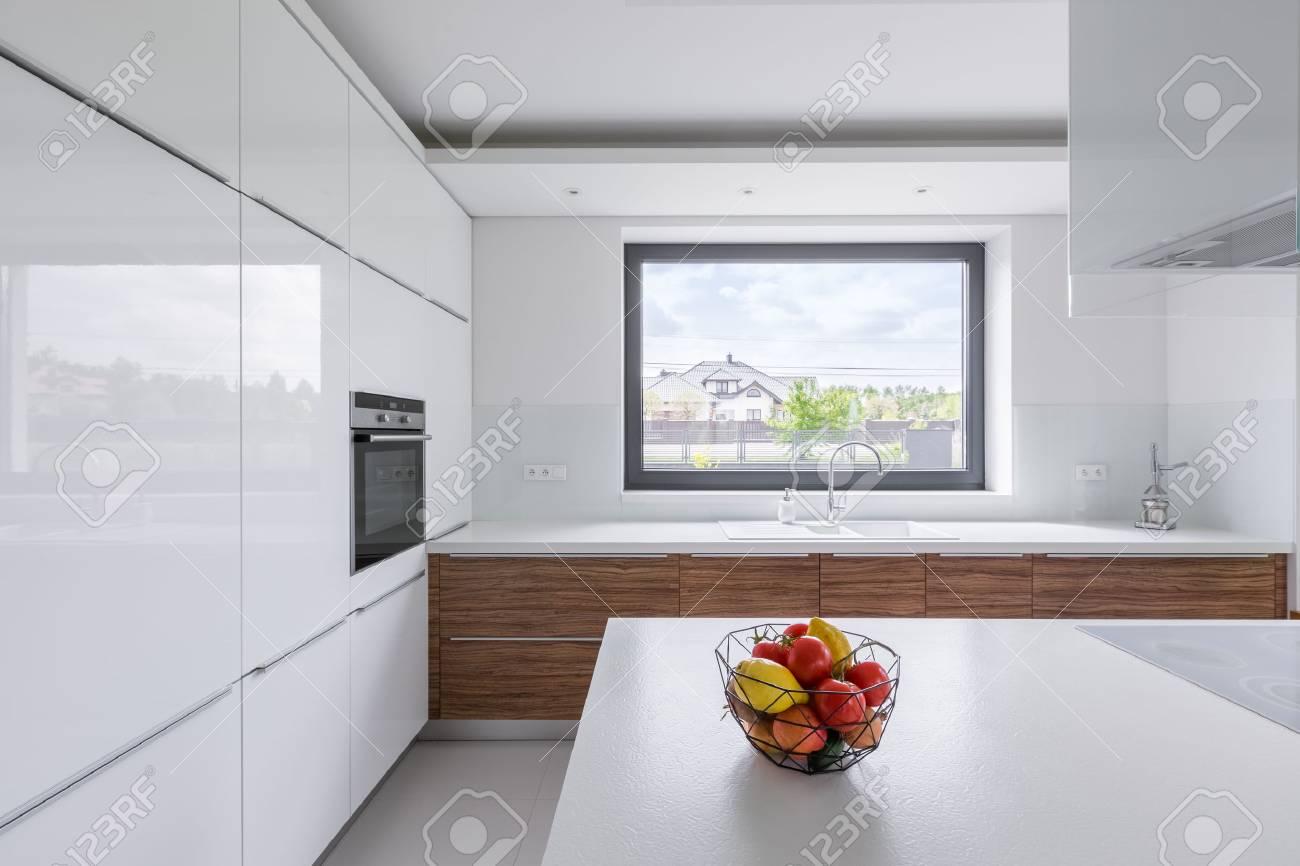 Design moderne, cuisine blanche avec îlot et grande fenêtre