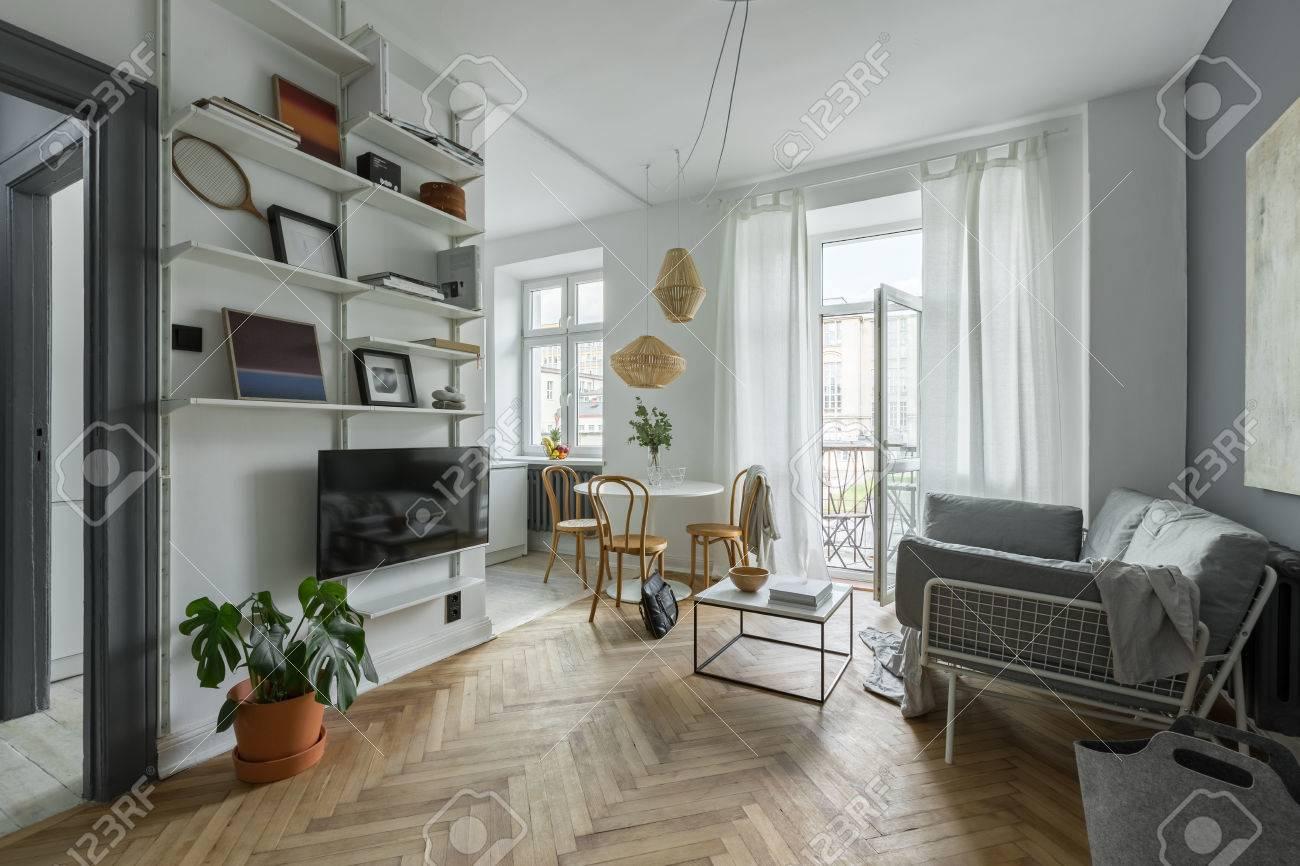 Grau Weißes Wohnzimmer Mit Balkon, Tisch Und Fernseher Standard Bild    82254008
