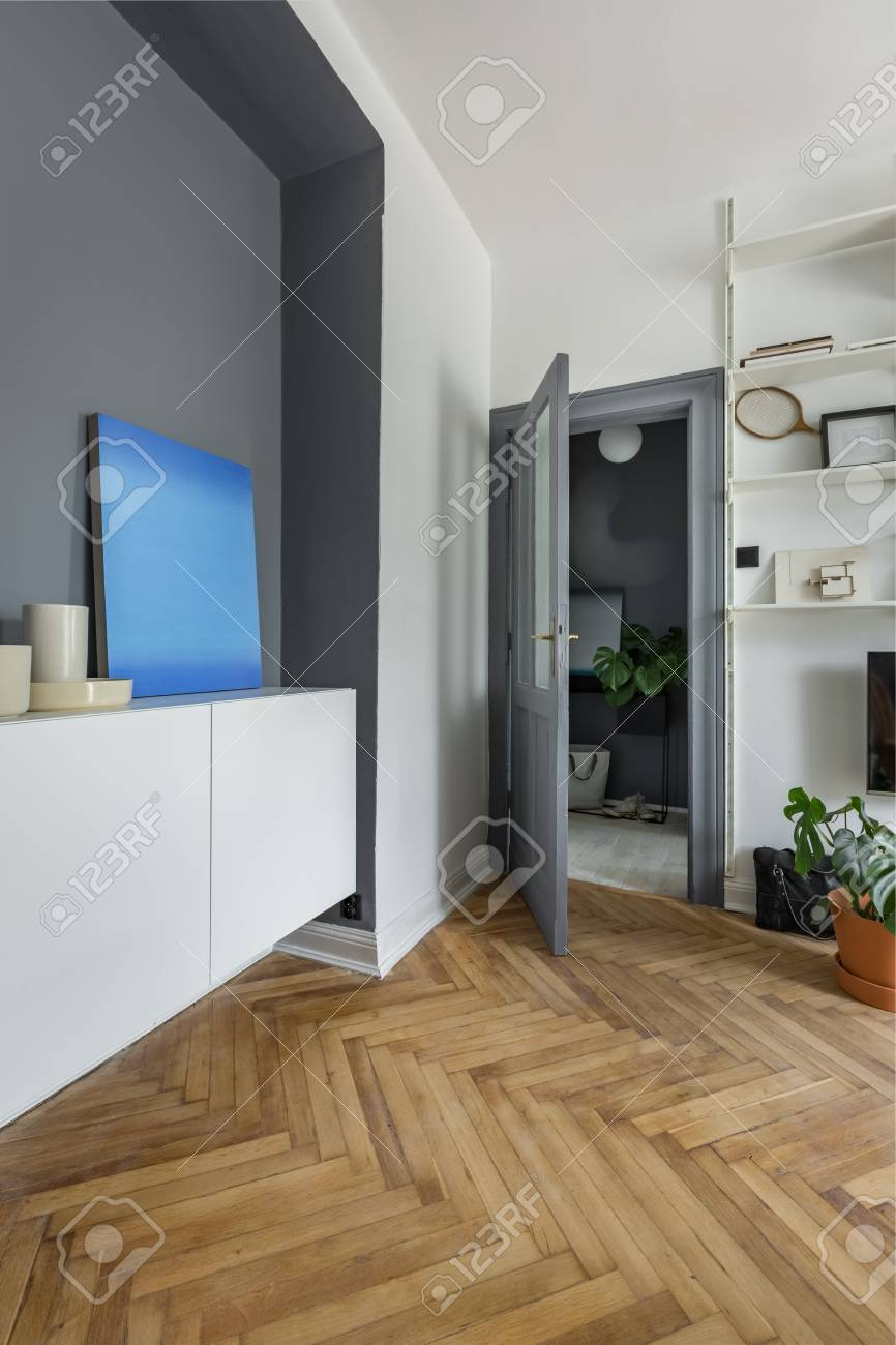 Chambre grise avec étagère blanche, armoire et peinture moderne