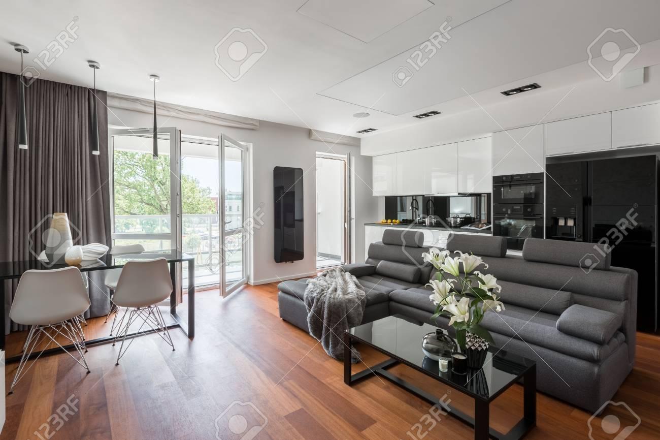 Salon contemporain avec canapé gris, table et balcon