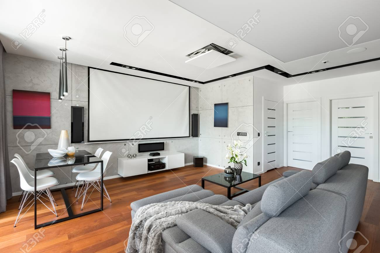 Salle de cinéma moderne avec écran de projection, canapé gris, table noire  et chaises blanches
