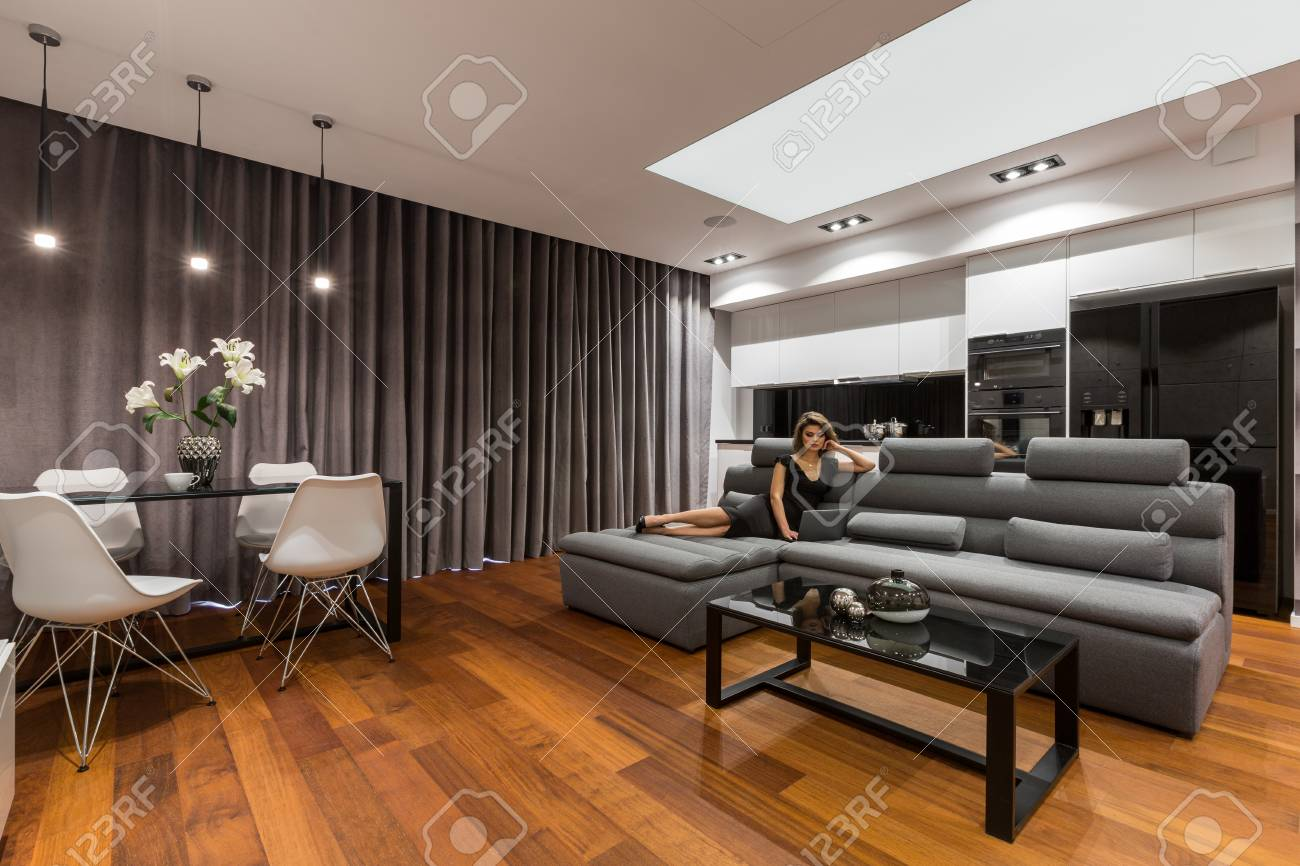 Woman Lying On Gray Sofa In Modern Apartment With Dining Table ...